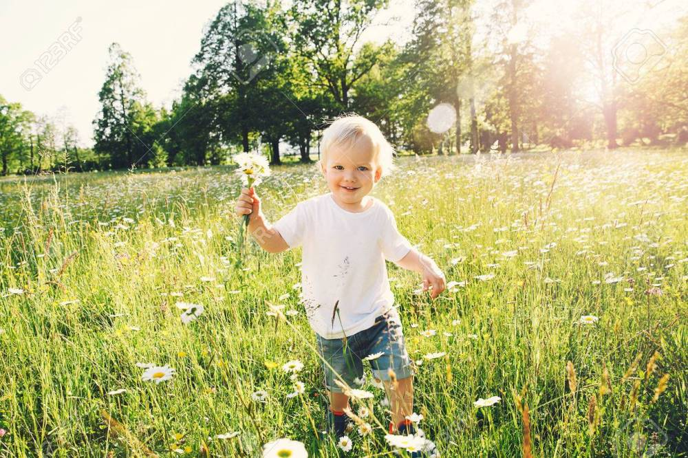 Happy child running on meadow of flowers