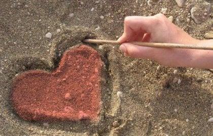 Mano-dibujando-un-corazón-en-la-arena-420x269